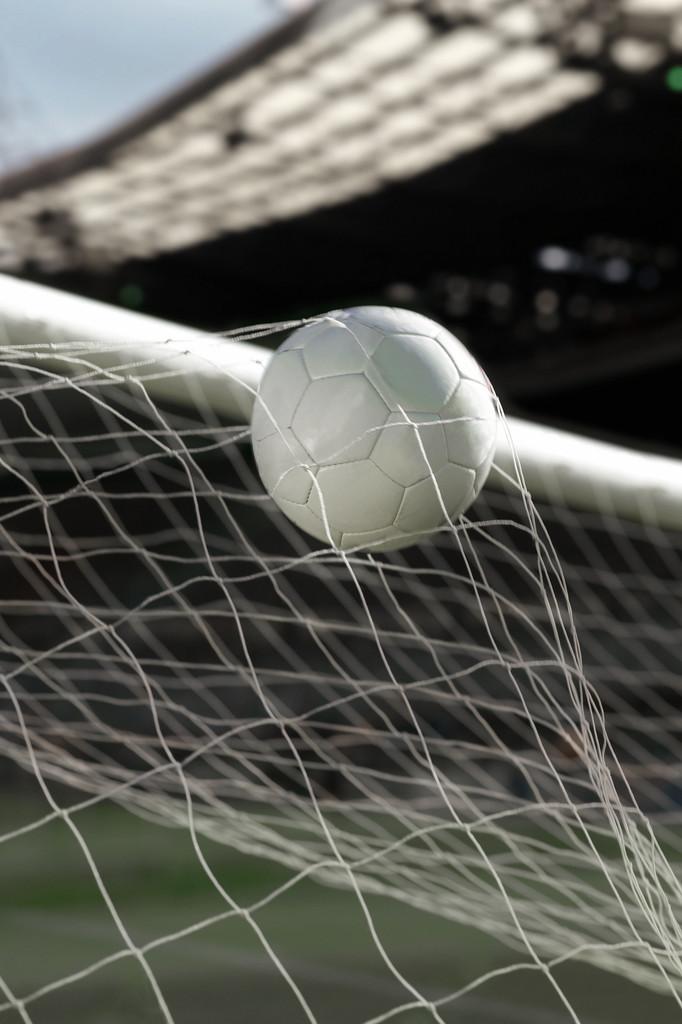 Soccer ball entering the net